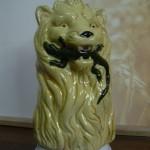 Broc barbotine Lion tenant un lézard dans sa gueule. Fond ocre. Hauteur 20cms