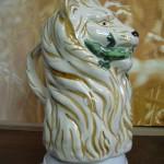 Broc barbotine Lion tenant un lézard dans sa gueule. Fond naturel. Hauteur 20cms