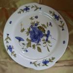 Plat rond avec oreillons. Décor composition florale bleu cobalt et vert brun.